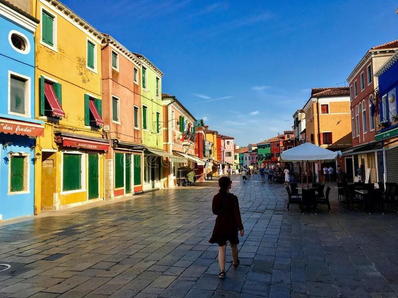 A female tourists exploring the colourful streets of Burano, Italy, on a beautiful quiet summer morning. royalty free stock photography