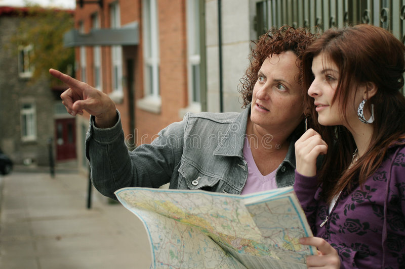 Female tourists orienteering. Two female tourists reading a map, trying to get their bearings in an unfamiliar city stock image