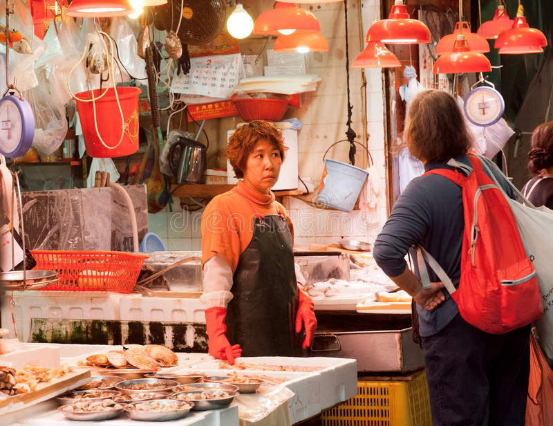 Female traders of fish market spread seafood for sale on a street tray royalty free stock photos