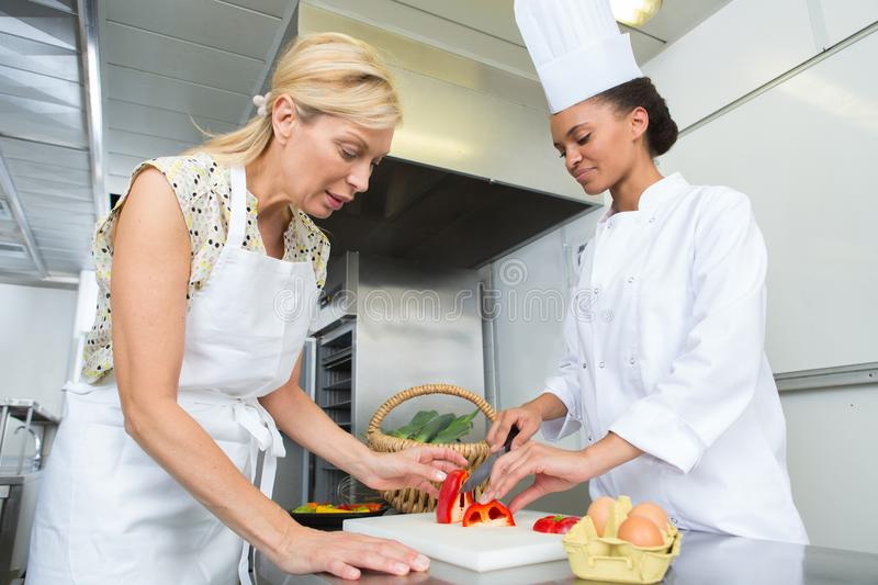 Female trainee chef chopping peppers. Trainee royalty free stock image