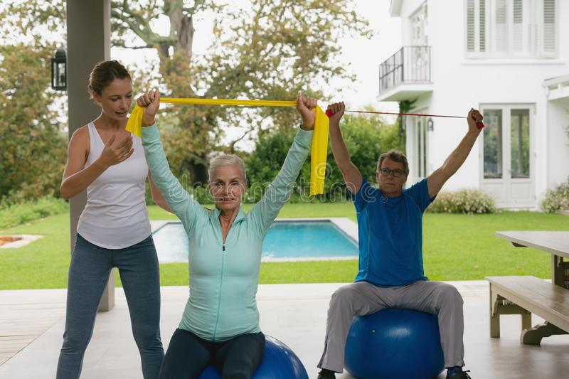 Female trainer assisting active senior couple to exercise with resistance band in the porch. Front view of Caucasian female trainer assisting active senior stock photos