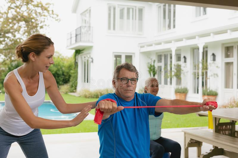 Female trainer assisting active senior couple to exercise with resistance band in the porch. Front view of Caucasian female trainer assisting active senior royalty free stock images