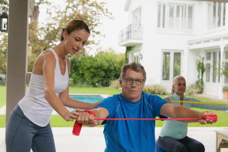 Female trainer assisting active senior couple to exercise with resistance band in the porch. Front view of Caucasian female trainer assisting active senior royalty free stock photos