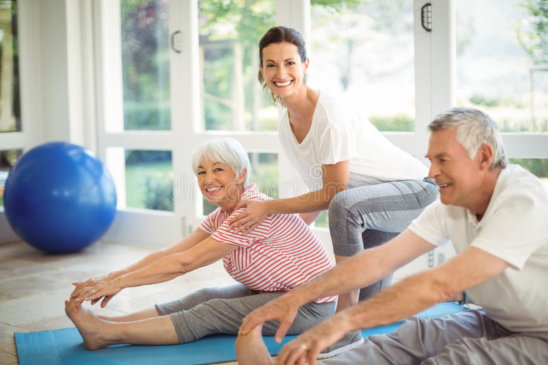 Female trainer assisting senior couple in performing exercise stock image