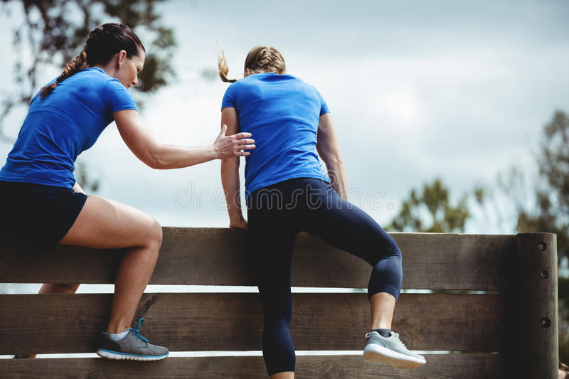 Female trainer assisting woman to climb a wooden wall stock images