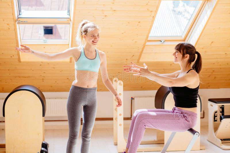 Female trainer assisting woman with stretching exercise with pilates reformer. Personal coaching young beautiful woman. royalty free stock photography