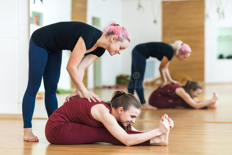 Young, attractive girls help each other to do a stretching exercise while she sits in the split on the floor in the gym. They are royalty free stock photography