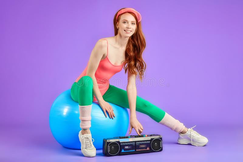 Young female trainer sits on fit ball and press button on portable cassette player. Female trainer sits on blue fitness ball and press the button on her portable royalty free stock image