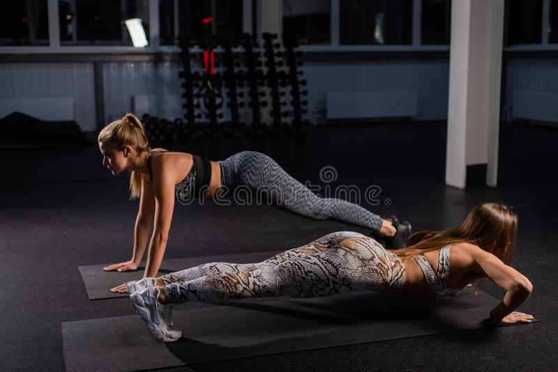 Female trainer teaches ward to do push-ups correctly. Beautiful woman trainer makes sure that her client, a young blonde. Female trainer teaches ward to do push royalty free stock photos