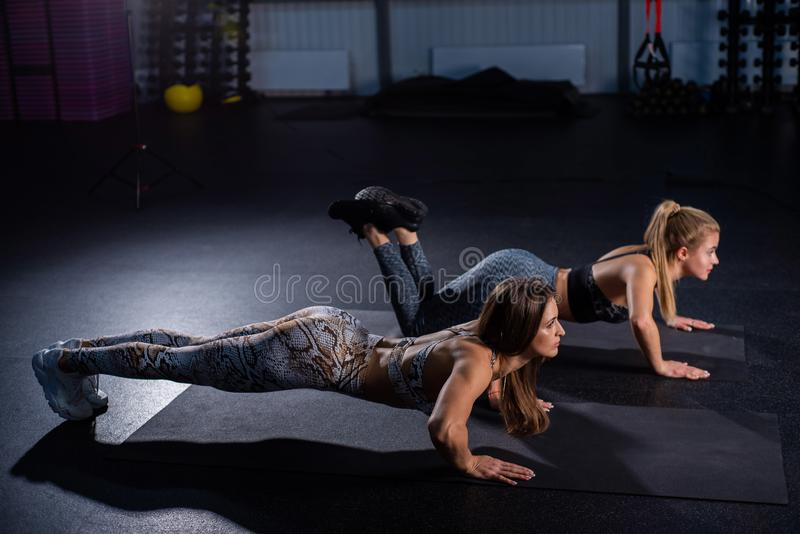 Female trainer teaches ward to do push-ups correctly. Beautiful woman trainer makes sure that her client, a young blonde. Female trainer teaches ward to do push royalty free stock image