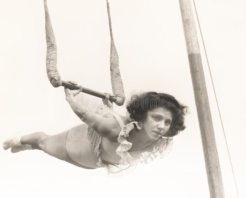 Female trapeze artist in mid-air royalty free stock photography