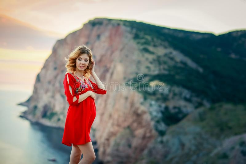 Female travel nature scenery landscape concept of lady in red dress stay on edge of mountain top above south sea in royalty free stock photography