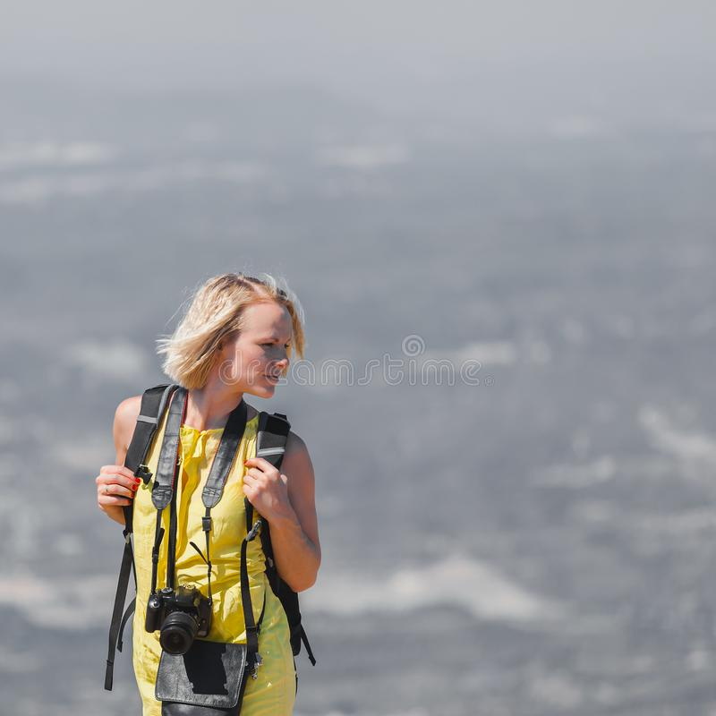 Female traveler with a backpack on her back enjoying the views from the mountains of Montserrat in Spain royalty free stock images