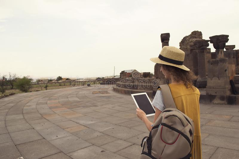 Female traveler with backpack holding tablet during visiting Zvartnots Armenia. Technology and traveling. Toned royalty free stock photos