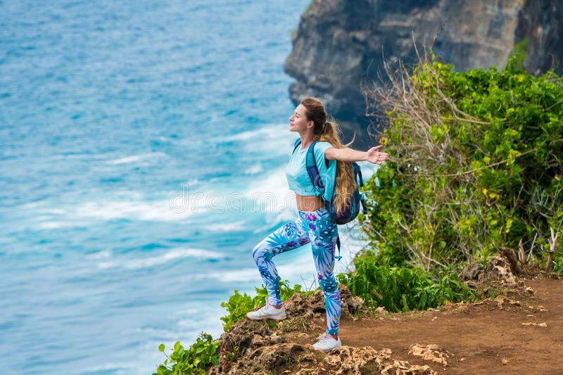 Female traveler with a backpack standing on the edge of a cliff and enjoying the view of the ocean. Bali, Indonesia royalty free stock images