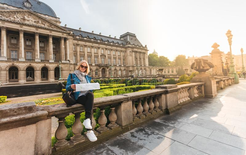 Female traveler sits on the parapet on the background of the Royal Palace in Brussels and looks into the map, Belgium stock photo