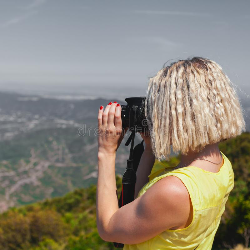Female traveler enjoying the views from the mountains of Montserrat in Spain and makes a photo stock image