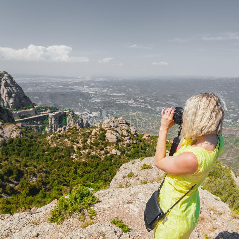 Female traveler enjoying the views from the mountains of Montserrat in Spain and makes a photo royalty free stock images