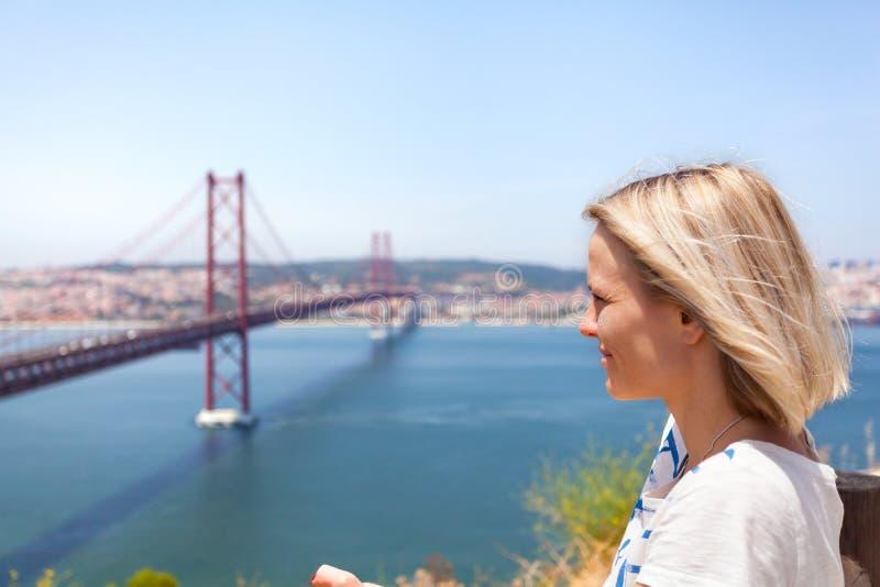 Female traveler enjoys panoramic views of Lisbon and the bridge of April 25 royalty free stock photo