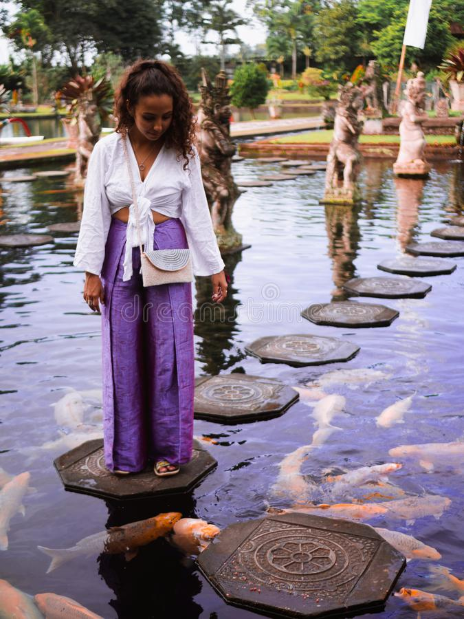 Solo Female Traveler Feeding Koi Fish on Stepping Stones around Koi Fish at Main fountain at Tirta Gangga, Bali. Female traveler feeding koi fish on stepping royalty free stock images
