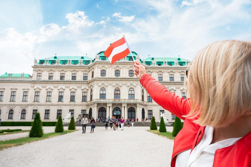 Female traveler with the flag of Austria against the backdrop of the Upper Belvedere Palace in Vienna. stock photo