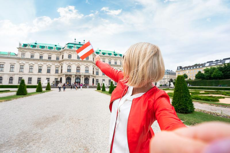 Female traveler with the flag of Austria against the backdrop of the Upper Belvedere Palace in Vienna. royalty free stock photo