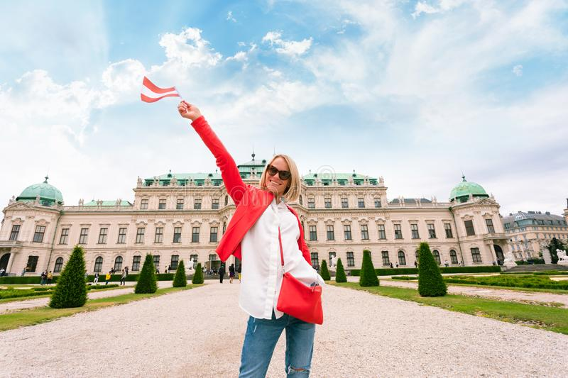 Female traveler with the flag of Austria against the backdrop of the Upper Belvedere Palace in Vienna. stock images