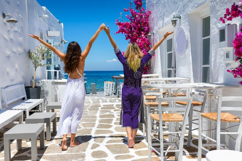 Female traveler friends on a classic summer settings of the cyclades in Greece stock photo