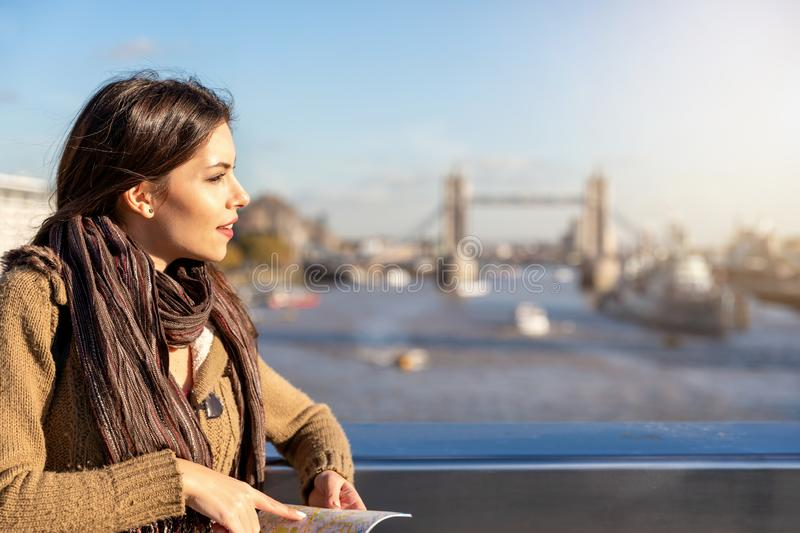 Female traveler in London in front of the Tower Bridge, United Kingdom. Attractive female traveler in London holding a city map in front of the Tower Bridge on a stock image