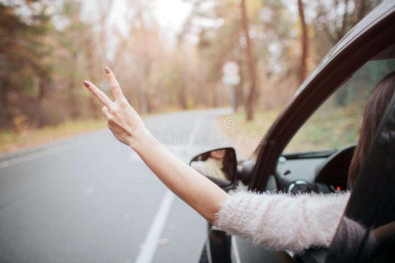 Female traveler on the road holding the sign of Victory. Fall vacation, holidays, travel, road trip and people concept stock photo