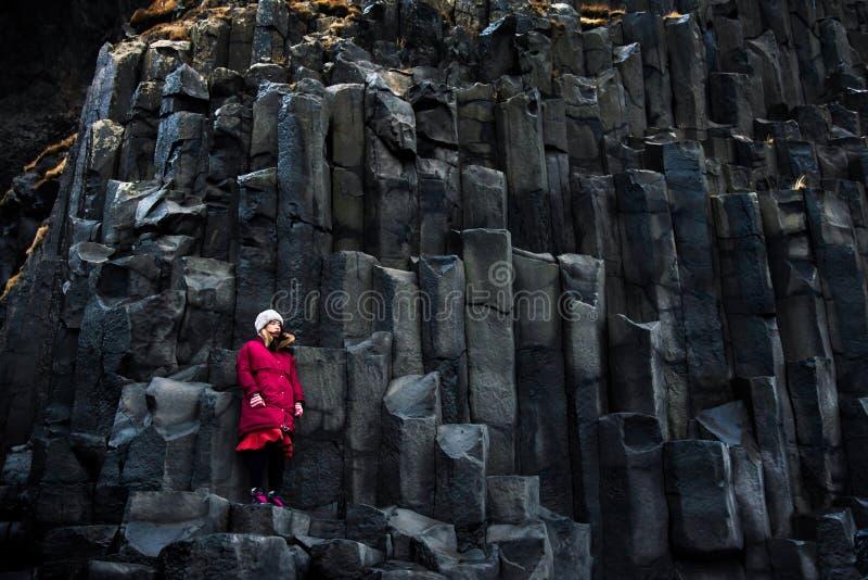 Female traveler on rocks of Black sand Reynisfjara Beach in Iceland royalty free stock photo