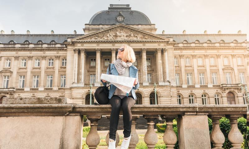 Female traveler sits on the parapet on the background of the Royal Palace in Brussels and looks into the map, Belgium royalty free stock photos