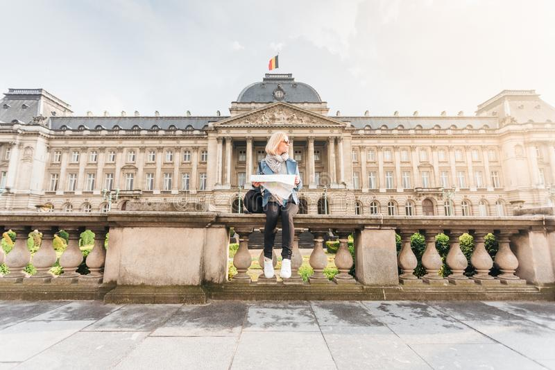Female traveler sits on the parapet on the background of the Royal Palace in Brussels and looks into the map, Belgium royalty free stock photo