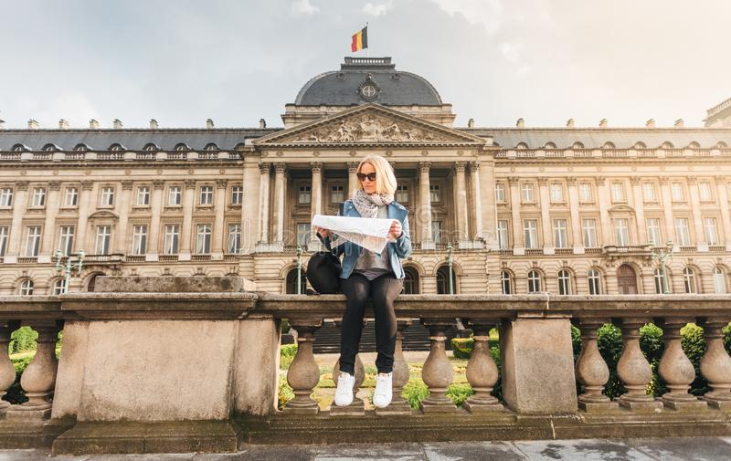 Female traveler sits on the parapet on the background of the Royal Palace in Brussels and looks into the map, Belgium stock image