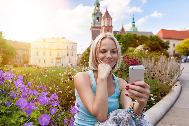 Female traveler sitting and looking in a mobile phone on the background of Wawel Castle royalty free stock photo