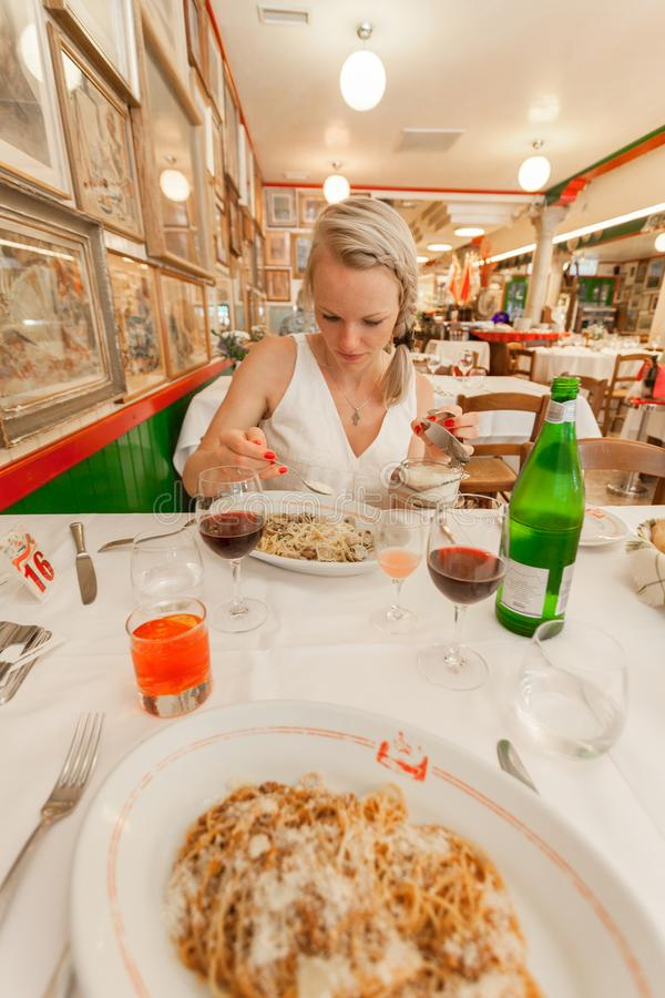 A female traveler is sitting in a restaurant on the island of Burano and is going to eat her pasta with seashells stock photography