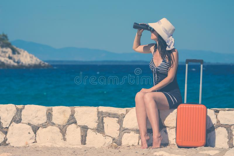 Female tourist with binoculars and luggage at the seaside. Summer vacation and travel concepts. royalty free stock images