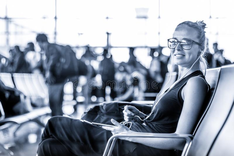 Female traveler using her cell phone while waiting to board a plane at departure gates at asian airport terminal. Blue. Casual sporty young blond female traveler royalty free stock images