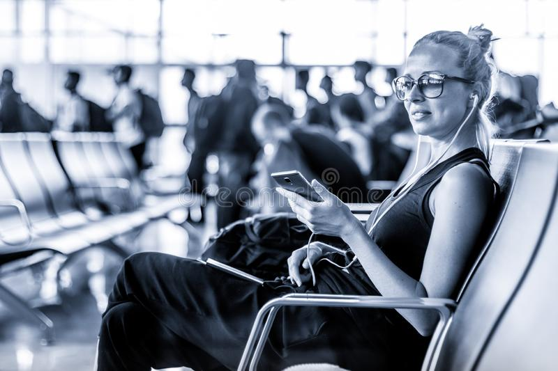 Female traveler using her cell phone while waiting to board a plane at departure gates at asian airport terminal. Blue. Casual sporty young blond female traveler stock image