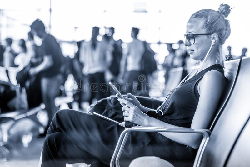 Female traveler using her cell phone while waiting to board a plane at departure gates at asian airport terminal. Blue. Casual sporty young blond female traveler stock photos
