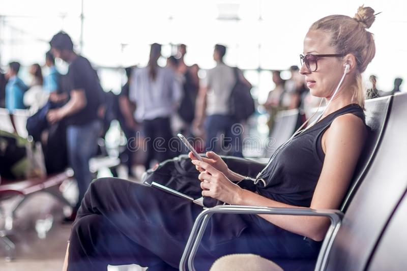 Female traveler using her cell phone while waiting to board a plane at departure gates at asian airport terminal. Casual sporty young blond female traveler stock photography