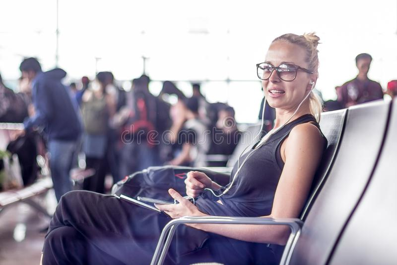 Female traveler using her cell phone while waiting to board a plane at departure gates at asian airport terminal. Casual sporty young blond female traveler royalty free stock photo