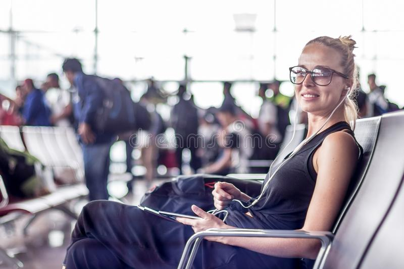 Female traveler using her cell phone while waiting to board a plane at departure gates at asian airport terminal. Casual sporty young blond female traveler royalty free stock photos