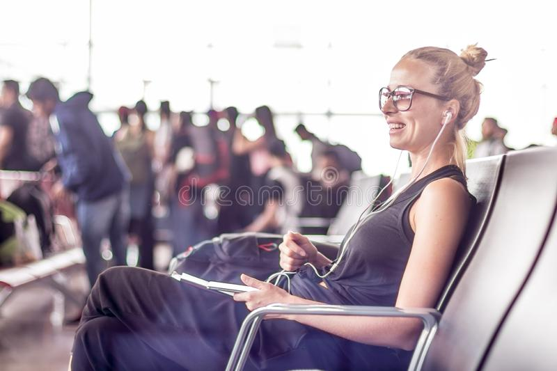 Female traveler using her cell phone while waiting to board a plane at departure gates at asian airport terminal. Casual sporty young blond female traveler royalty free stock image