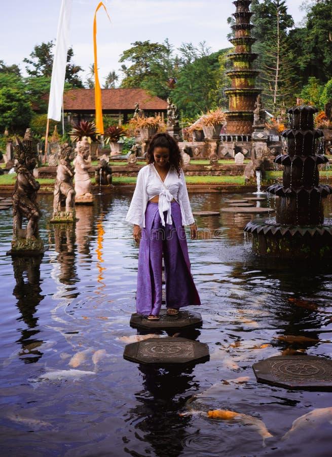 Solo Female Traveler Walking on Stepping Stones around Koi Fish at Main fountain at Tirta Gangga, Bali. Female traveler walking on stepping stones feeding koi royalty free stock image