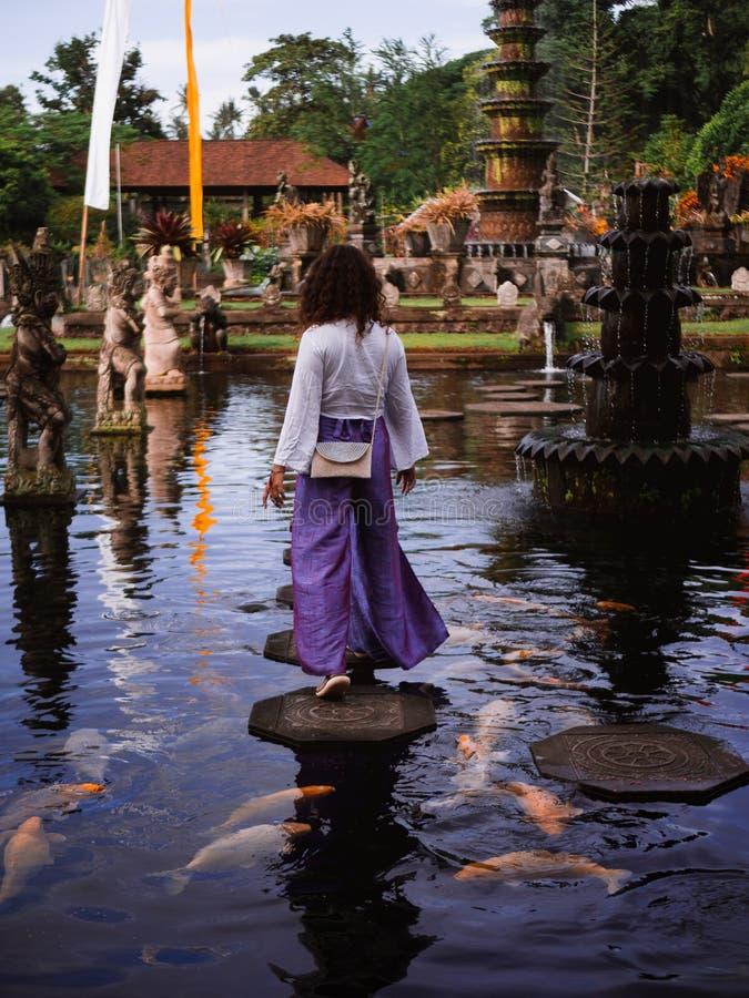 Solo Female Traveler Walking on Stepping Stones around Koi Fish at Main fountain at Tirta Gangga, Bali. Female traveler walking on stepping stones feeding koi royalty free stock images