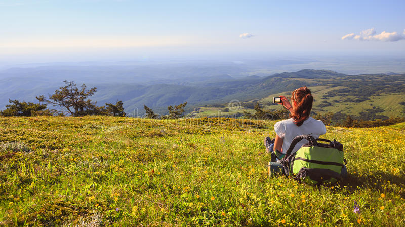 Female traveller with backpack making photo of mountain lanscape under blue sky. Young female traveller with backpack and long brown hair sitting at green grass stock images