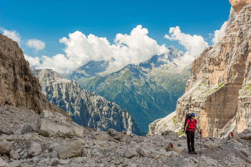 Female trekker walking along mountain valley. royalty free stock images