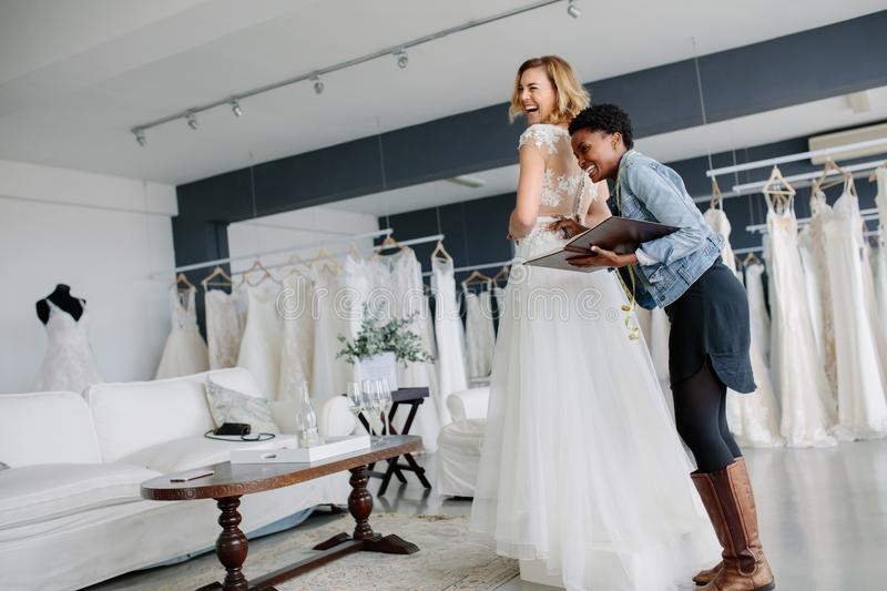 Female trying on wedding gown with women assistant in shop royalty free stock image