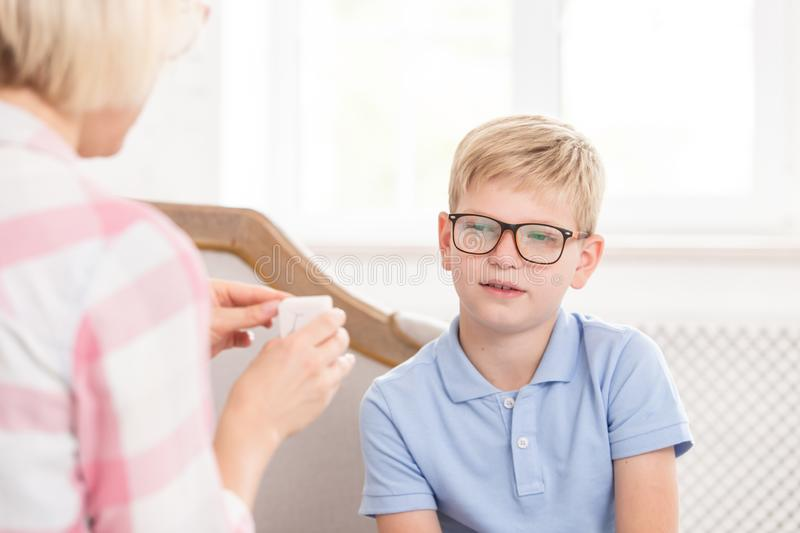 Female tutor asking her pupil to translate word, writed on card. Young boy trying to remeber translation. They are royalty free stock images